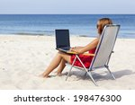 Woman is sitting with laptop on the beach. - stock photo