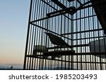 Small photo of The blue afternoon sky mingled with the bright orange with the caged bird