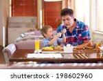 Boy Feeding Father In Restaurant