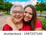 Small photo of Beautiful Latin grand mother with her grand daughter. Brazilian family.