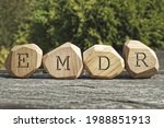 Small photo of Letters EMDR written on wooden irregular blocks. Eye Movement Desensitization and Reprocessing psychotherapy treatment concept.