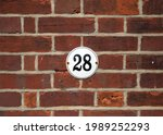 number 28 on old red brick wall.... | Shutterstock . vector #1989252293