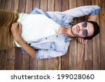 young man lying on a wooden... | Shutterstock . vector #199028060