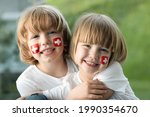 Brothers with Swiss Flags on their cheeks celebrating Swiss National Day.