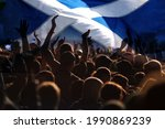 Small photo of football fans supporting Scotland - crowd celebrating in stadium with raised hands against Scotland flag
