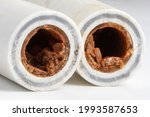 Small photo of Old broken sludge plumbing polypropylene pipes with red rust and limescale. Corrosion, sludge and hard water concept