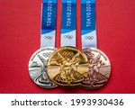 Small photo of April 25, 2021 Tokyo, Japan. Gold, silver and bronze medals of the XXXII Summer Olympic Games in Tokyo on a red background.