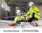 Small photo of Accident at construction site. Physical injury accident at work of construction worker. First Aid Help construction worker who has an accident at a construction site. had an accident unconscious.