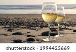 Two Wineglasses On Sandy Ocean...