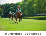 Stock photo race horses with jockeys on the home straight 199485986