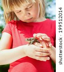 Small photo of Little girl looking at true toad sitting on her hand