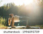 Young Woman Practicing Yoga In...