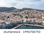 Syros island, Greece, Ermoupolis and Ano Siros town aerial drone view. cloudy blue sky background. Hermoupolis cityscape, from harbour up to the hills