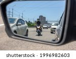 Small photo of The reflection of a motorcycle in the left side mirror of a car traveling in traffic and preparing to overtake between two cars in a narrow side distance at speed. Provoking a traffic incident.