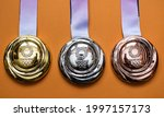 Small photo of April 25, 2021 Tokyo, Japan. Gold, silver and bronze medals of the XXXII Summer Olympic Games in Tokyo on a yellow background.
