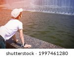 Boy leaning on the fountain side and looking at the water, wearing white T-shirt and cap, view from the back