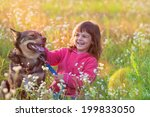Stock photo happy little girl with big dog sitting in the lawn 199833050