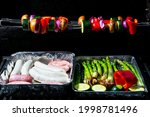 a gas grill with vegetables and ...