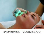 Small photo of Beautician doing led light therapy to woman in SPA salon, facial phototherapy for skin pore cleaning. Anti-aging treatments and photo rejuvenation procedure. Lady getting face therapy in SPA resort