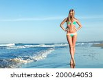 Young Woman Standing On Beach...
