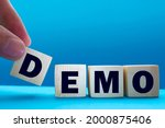 Small photo of Demo symbol. Concept word 'demo' on cubes on a beautiful dark wooden background. Businessman hand. Business and demo concept. Copy space.