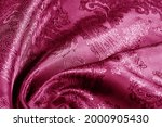 Small photo of red, blushing, ruddy, florid, gules, blushful fabric with a paisley pattern. based on traditional Asian elements.texture, background, green