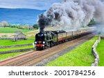 The locomotive smokes and rushes along the railway. Train ride on railroad. Locomotive smoke