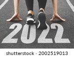 Small photo of close-up of female feet in sneakers at the start. Beginning and start of the new year 2022, goals and plans for the next year