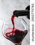red wine is pouring into glass... | Shutterstock . vector #2002775783