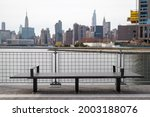 Empty Bench on the Greenpoint Brooklyn Riverfront along the East River with the Manhattan Skyline in the background