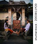 Small photo of Balinese culture. Multicultural couple wearing traditional Balinese clothing. Happy couple spending time together. Caucasian wife and Balinese husband. Romantic relationship. Penglipuran, Bali