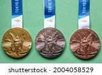 Small photo of April 25, 2021 Tokyo, Japan. Gold, silver and bronze medals of the XXXII Summer Olympic Games in Tokyo on a green background.