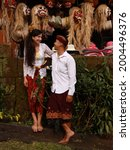 Small photo of Balinese culture. Multicultural couple wearing traditional Balinese clothing. Wooden masks. Caucasian wife and Balinese husband. Romantic relationship. Penglipuran, Bali, Indonesia