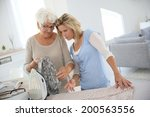 elderly woman with housekeeper... | Shutterstock . vector #200563556