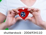 Woman in white t-shirt holds a heart in the form flag Tennessee on her chest. Photo for a postcard on Flag Day, Independence Day, travel, patriotism, other holiday