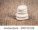 Pyramid of zen stones on a wooden board - stock photo