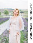 Small photo of Charming likable mature blond woman in elegant beige long dress posing in lavender field. Middle aged lady in dress outdoors.