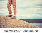 feet man standing on rocky...