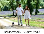 Stock photo young happy man and woman couple walking with their dog in summer vacation in countryside 200948930