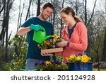 Smiling Young Couple Watering...