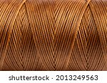 Small photo of A spool of brown thread in close-up. Waxed brown sewing thread for leather products. Brown thread.