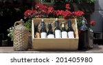 Wine In Old Bottles On A Barrel.