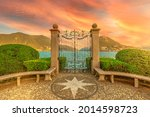 Gate on the Lugano Lake in the public Ciani park of Switzerland. Red sunset by the lakefront of Lugano city in Ticino canton. Park bench with wind rose of stones and with Monte San Salvatore mount.