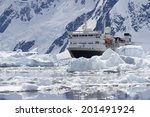 big blue tourist ship in the ice of the Antarctic mountains in the background of the Antarctic Peninsula