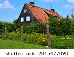 A view of an old house made out of wooden planks, logs and boards with an angled roof made out of red tiles seen next to a well maintained garden full of herbs, shrubs, trees and other flora in Poland