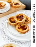 Small photo of Pastel de nata served for breakfast, typical Portuguese puff pastry - pasteis - egg tarts baked and ready to eat
