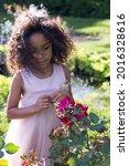 Vertical selective focus medium portrait of beautiful little windswept mixed-raced  girl in pink dress examining a rosebush