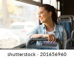Small photo of beautiful young woman taking bus to work