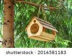 A Wooden Birdhouse Hangs On A...