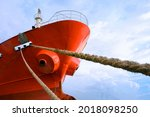 Low angle view of cargo ship docked at port with mooring rope against white clouds on blue sky background